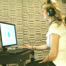 student in a sound booth wearing headphones